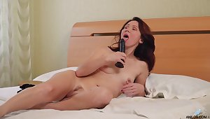Alluring redhead uses gloved hands to blur err her twat before hot toy play